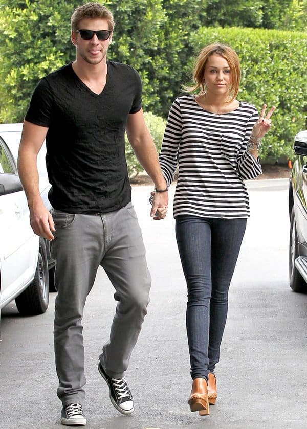 Miley Cyrus wearing high-heeled clog shoes and holding hands with her Liam Hemsworth in Toluca Lake, Los Angeles, on June 8, 2010