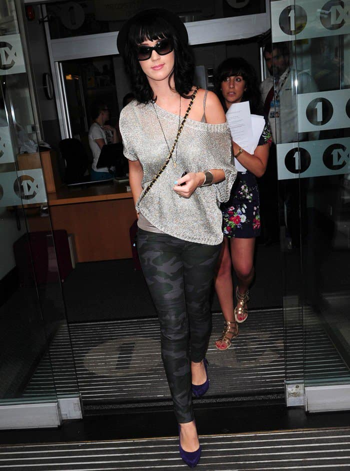 Katy Perry in camouflage leggings, a black fedora, a glittery metallic off-shoulder sweater from Vince, and purple suede pumps from Rock & Republic