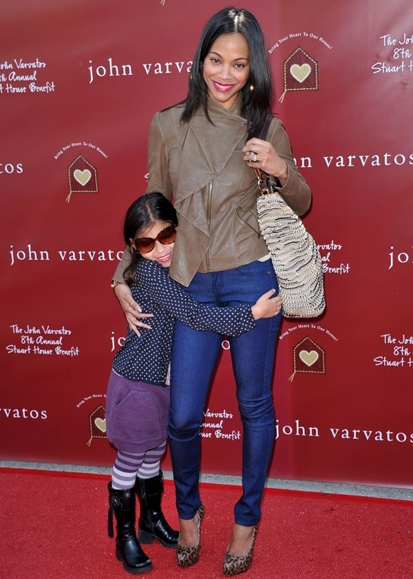 Zoe Saldana posing with her daughter for the cameras at the John Varvatos Eighth Annual Stuart House Benefit held at the John Varvatos Store in West Hollywood, California, on March 13, 2011