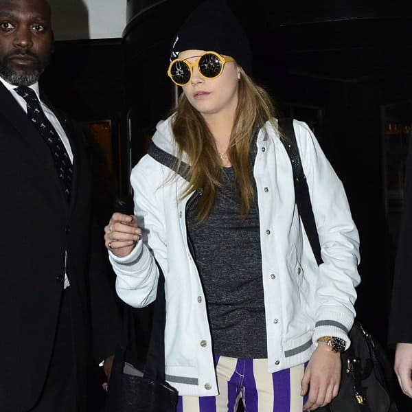 Cara Delevigne wears a varsity jacket during London Fashion Week