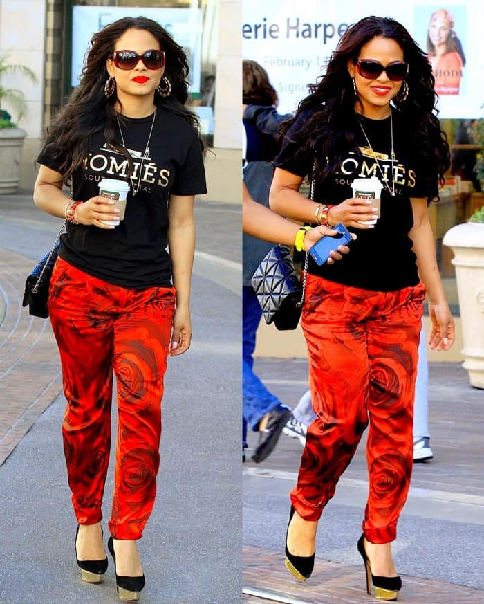 Christina Milian sported a casual Brian Lichtenberg black tee with gold text print paired with and Alice + Olivia Arthur silk red floral pants
