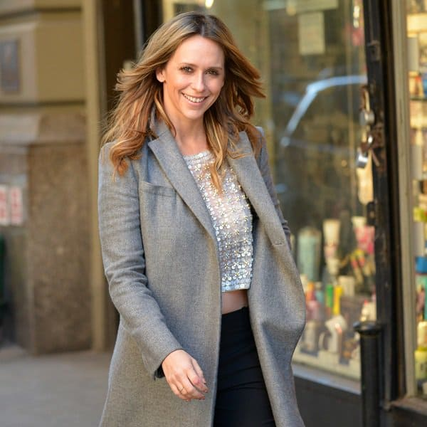 Jennifer Love Hewitt wears a gray wool trench coat over an embellished cropped top