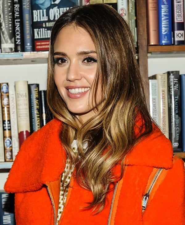 Jessica Alba wearing a bright orange moto jacket