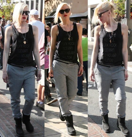 Gwen Stefani sported a casual yet edgy outfit consisting of a black tank top, printed loose trousers, and a pair of black boots