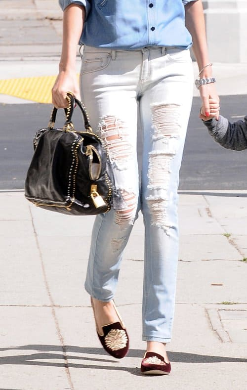 Miranda Kerr wears a chambray button-down top, ripped denim pants, and smoking flats
