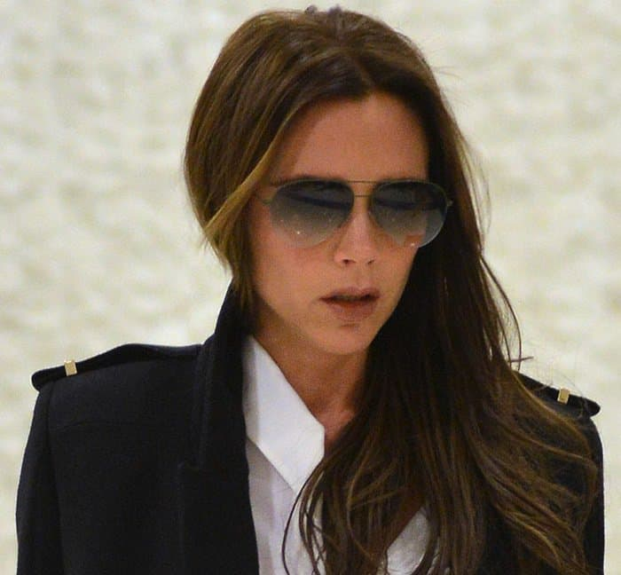 Victoria Beckham in a black trench coat worn over a white button-down top