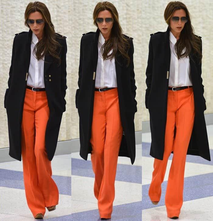 Victoria Beckham wears bright orange flare pants at JFK Airport