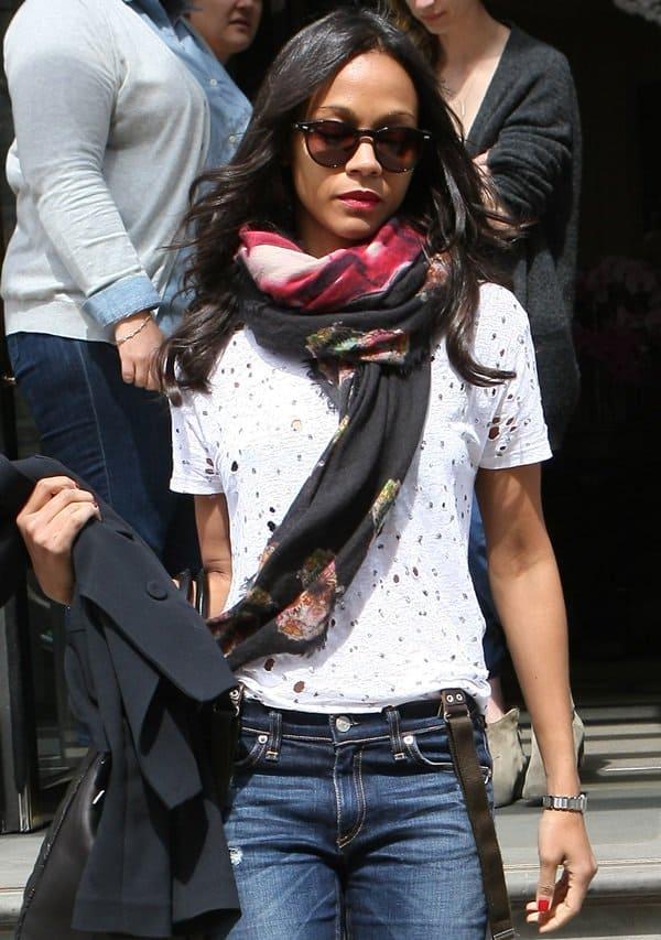 Zoe Saldana wears a wrap-around scarf outside the Corinthia Hotel in London