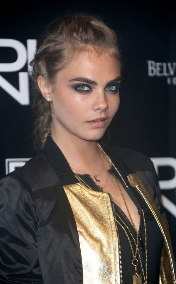 Cara Delevingne wearing a gold-accented black varsity jacket