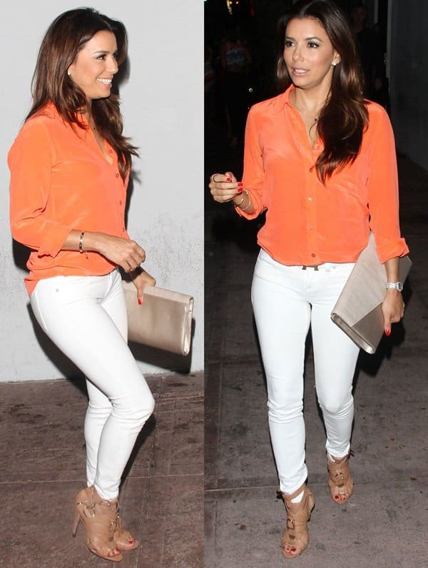 Eva Longoria flaunted her curvaceous body in a bright orange long-sleeve top, white skinny jeans, and brown strappy heels