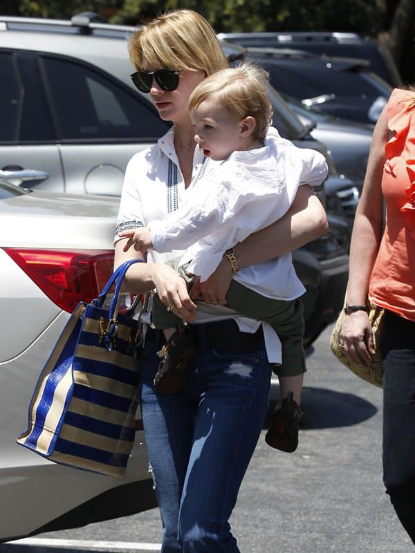 January Jones wearing bohemian style flared jeans with a white button-down blouse