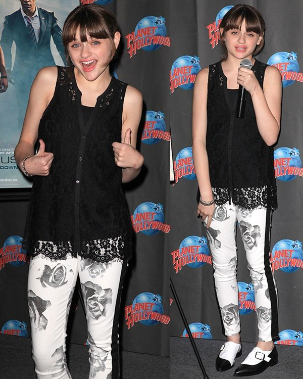 Joey King wearing a laced top, a pair of floral-printed jeans, and black-and-white shoes