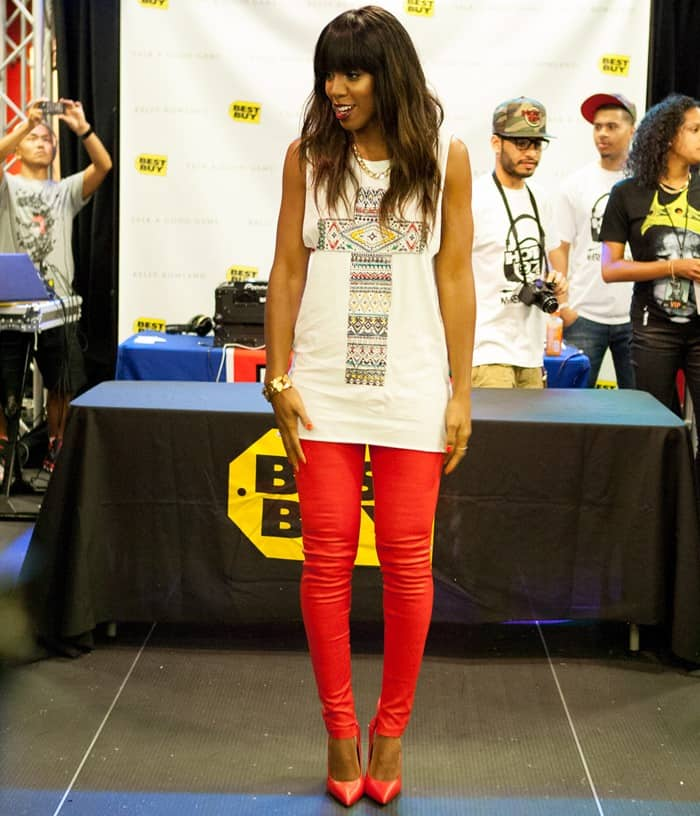 Kelly Rowland rocking an embroidered cross tank, red leather pants, red pumps, and gold chain jewelry