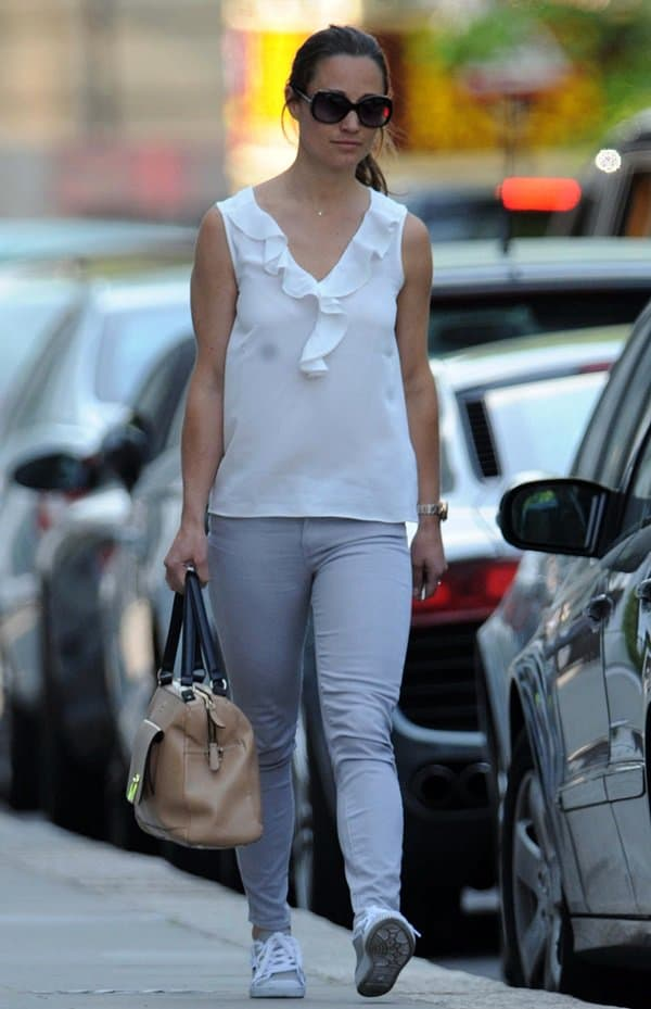 Pippa Middleton sported a white silk top, gray skinny jeans, sneakers, and a brown tote