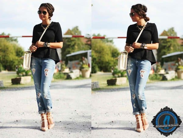 Anni wearing distressed boyfriend jeans with a structured peplum top