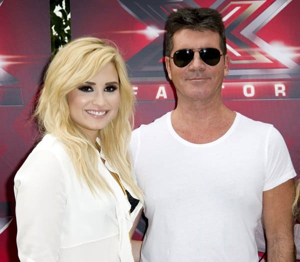 Demi Lovato posing with Simon Cowell