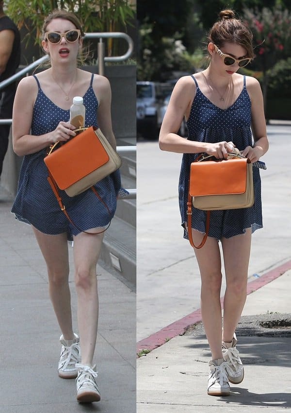 Emma Roberts accessorized with a pair of wedge sneakers, huge sunglasses, and an orange handbag that provided a complementing contrast to her blue romper
