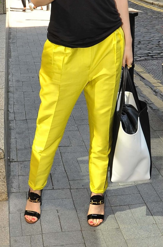 Jessie J wearing yellow pants with a black tank top and a pair of sandals