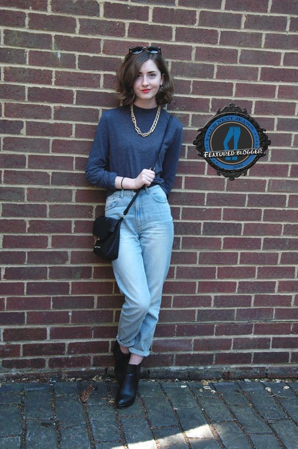 Xenia wears mom jeans with a solid-colored sweater