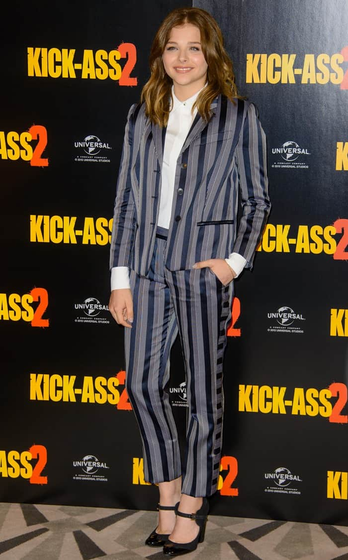Chloe wearing a pinstripe grey and black Viktor & Rolf suit with a white shirt and black Chanel Mary Janes