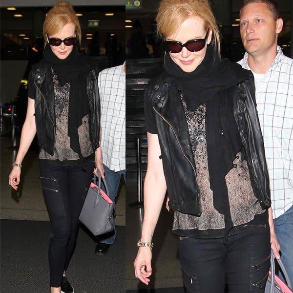 Nicole Kidman in an all-black ensemble, clutching a Christian Dior purse and clad in a heavily zippered pair of Rag & Bone black denims