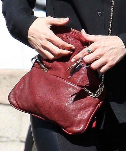 Emmy Rossum slung a red purse across her torso