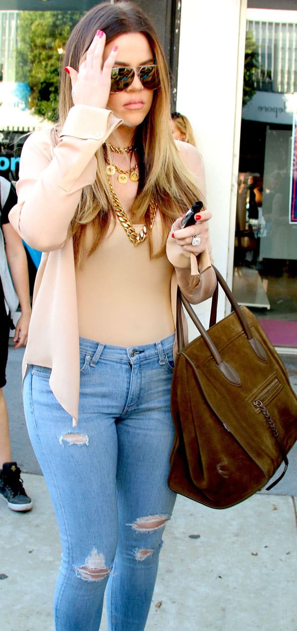 Kourtney Kardashian paired her jeans with a beige two-piece shirt-and-tank set, which she dressed up with some heavy duty gold accessories