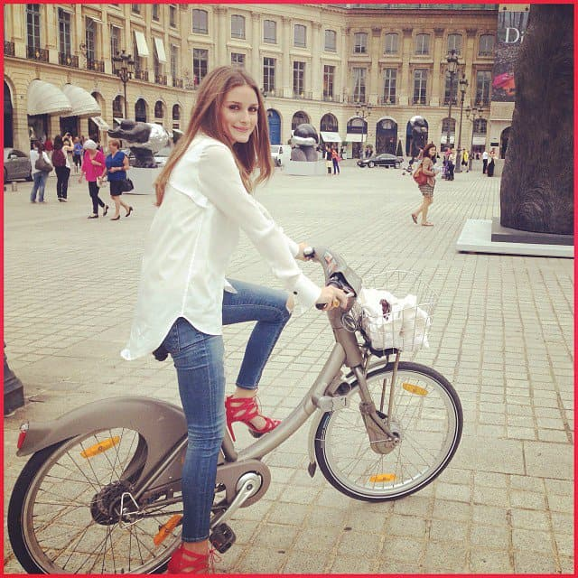 Olivia Palermo bicycles in sky-high red heels and jeans