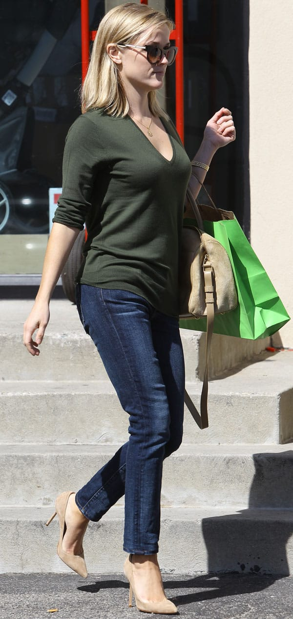 Reese Witherspoon wore her denims with a green scoop-neck top, a pair of nude heels, and a structured bag in the same nude hu
