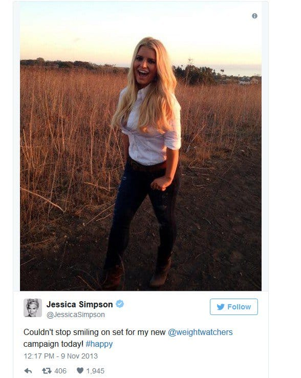 Jessica Simpson showing off her flat stomach in a white button-down shirt