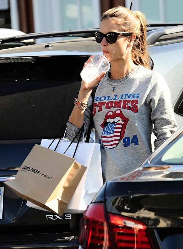 Alessandra Ambrosio wears a Rock Your Saturday Rolling Stones sweatshirt while shopping in Brentwood
