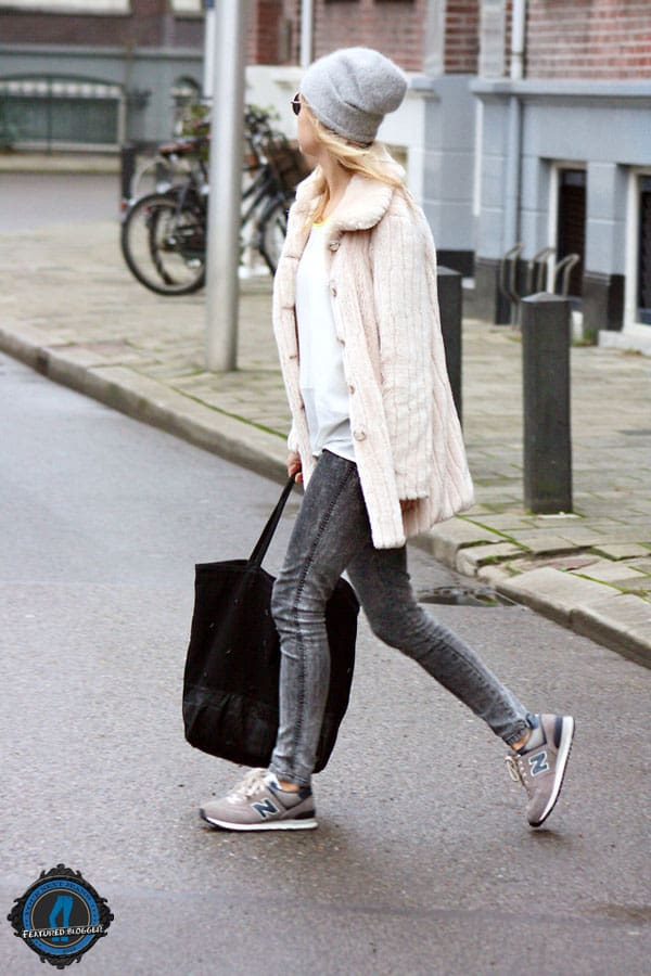 Jint wears New Balance sneakers with jeans and a feminine jacket