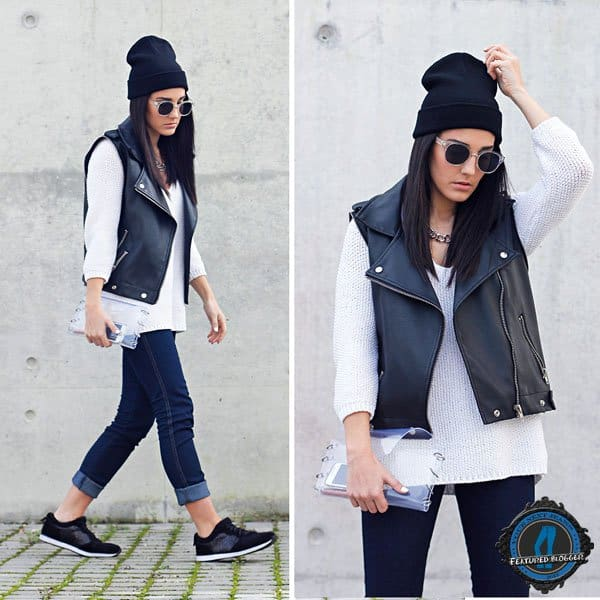 Maria wears a leather vest with a beanie, jeans, and sneakers