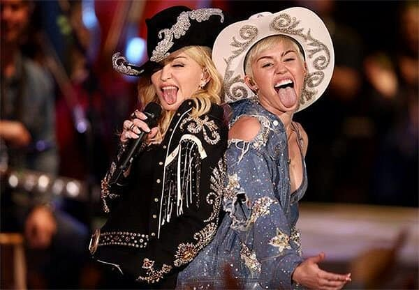 Madonna and Miley Cyrus sticking their tongues out in the finale of Miley Cyrus' MTV Unplugged concert, filmed at Sunset Gower Studios in Los Angeles, California, and aired on January 29, 2014