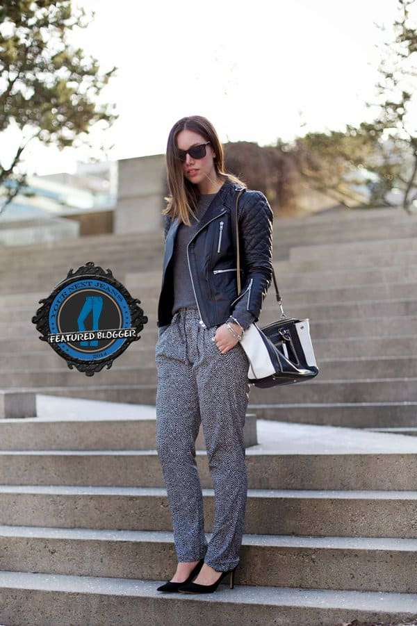 Alexandra with medium length hair in a leather jacket and masculine drawstring pants