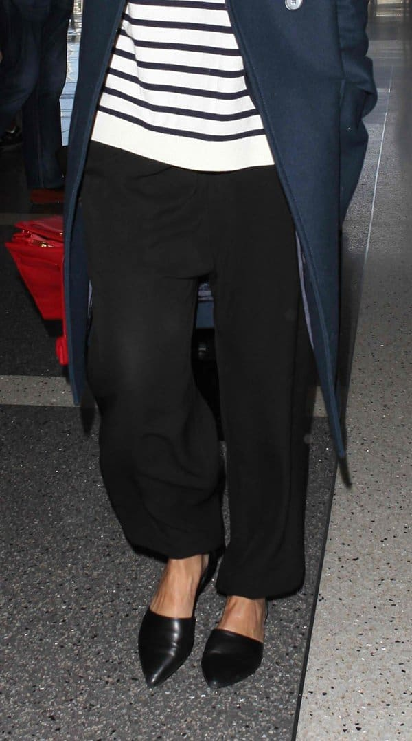 Jessica Alba wearing slouchy black pants with a Breton-striped top and a knee-length coat