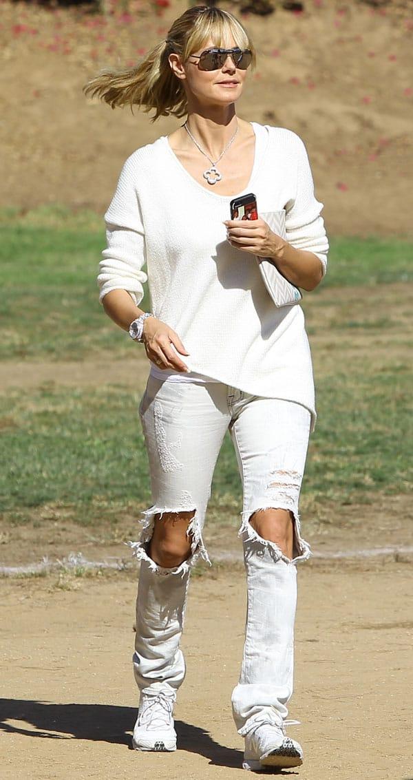 Heidi Klum wears ripped white jeans with an asymmetrical hem Helmut Lang sweater