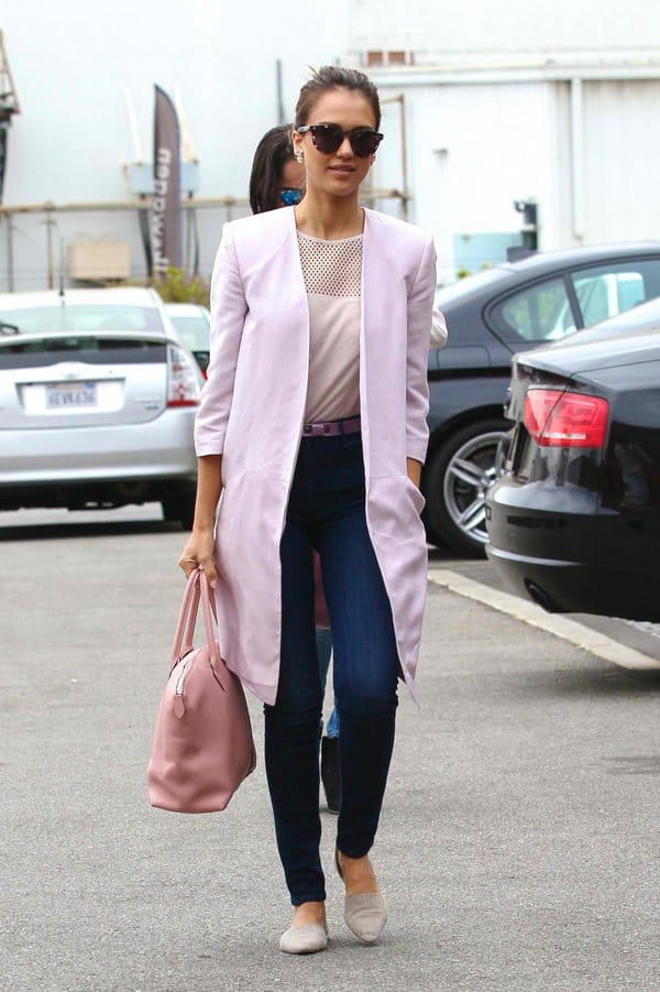 Jessica Alba wears high-waisted denim jeans with a perforated top