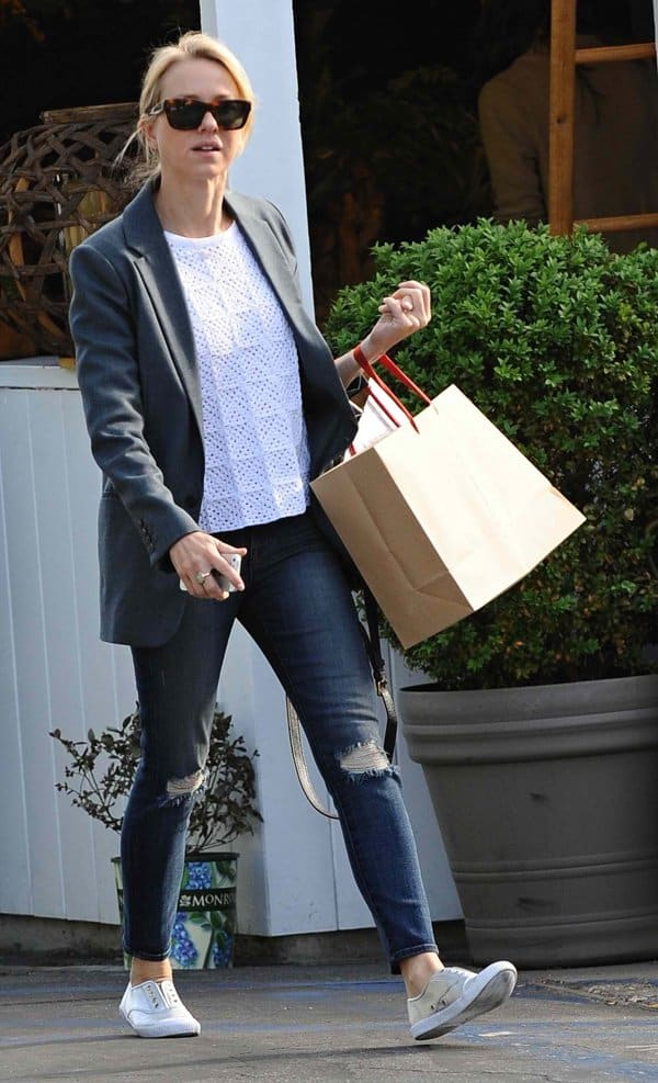 Naomi Watts wears ripped casual jeans with a structured blazer and metallic sneakers