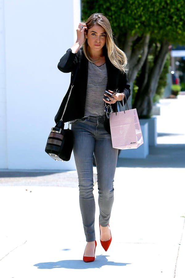 Nikki Reed wears high-waisted grey denim jeans with a summery striped top and a black blazer