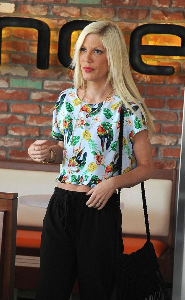 Tori Spelling wearing drawstring pants with a printed cropped shirt