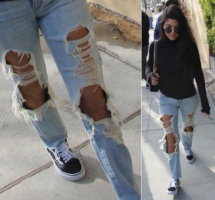 Kourtney Kardashian in distressed jeans and a black turtleneck paired with Vans 'Old Skool' sneakers