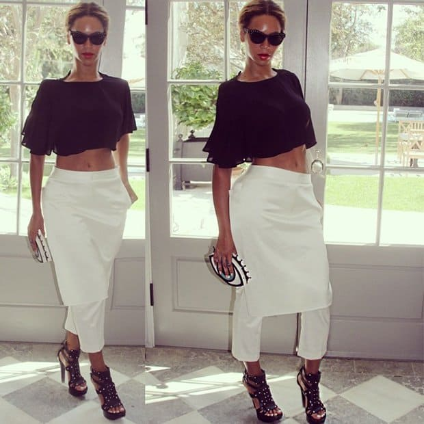 Beyonce wearing a ruffled crop top, 3.1 Phillip Lim pants, studded platform sandals, and a Charlotte Olympia clutch