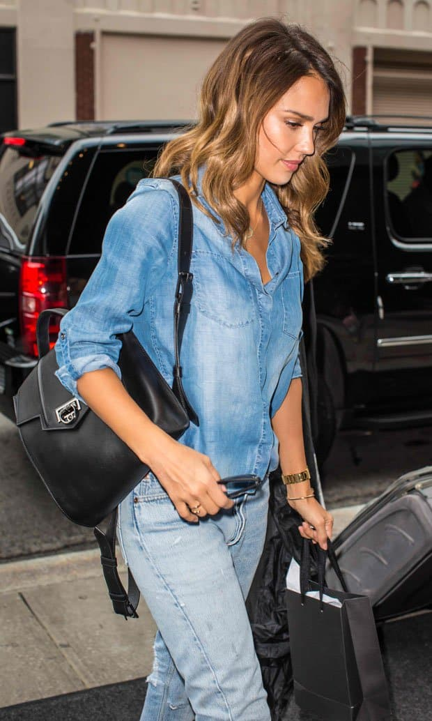 Jessica Alba carries a sleek Reece Hudson backpack styled in smooth leather with gunmetal-tone hardware