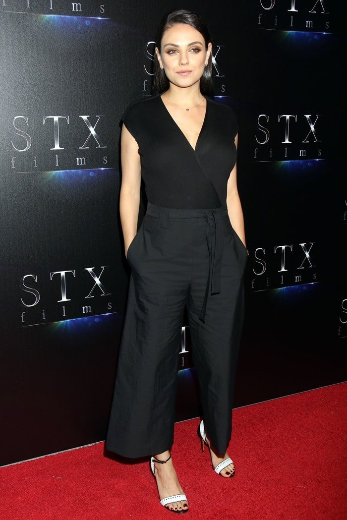 Mila Kunis in a belted Brunello Cucinelli jumpsuit with ribbed knit bodice and poplin legs