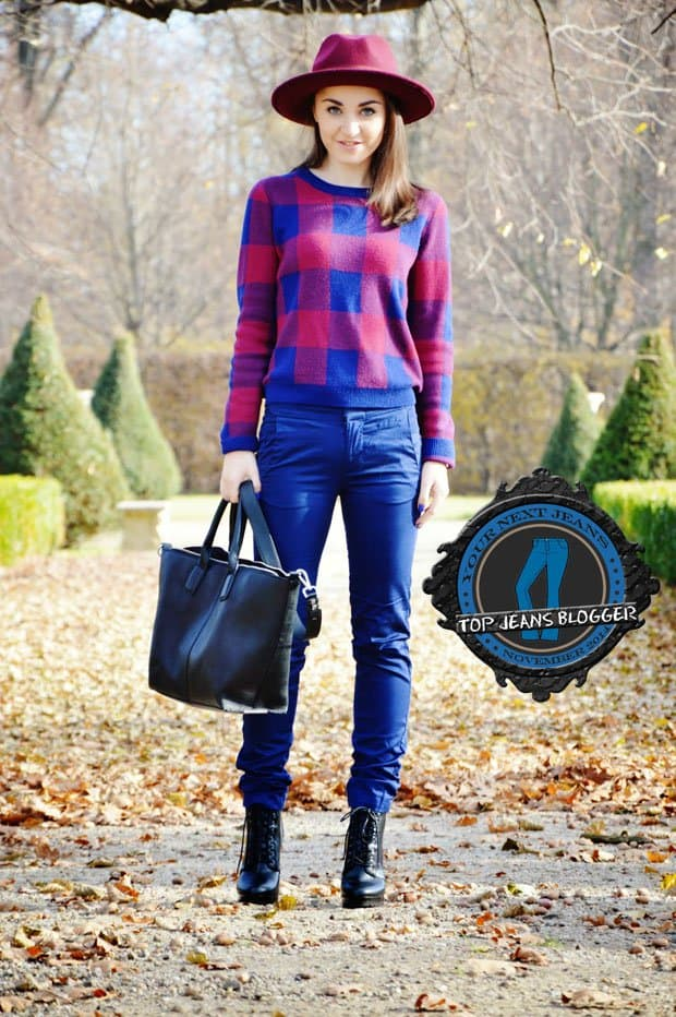 Malwina shows how to wear blue pants with a plaid sweater, a red hat, lace-up boots, and a tote bag