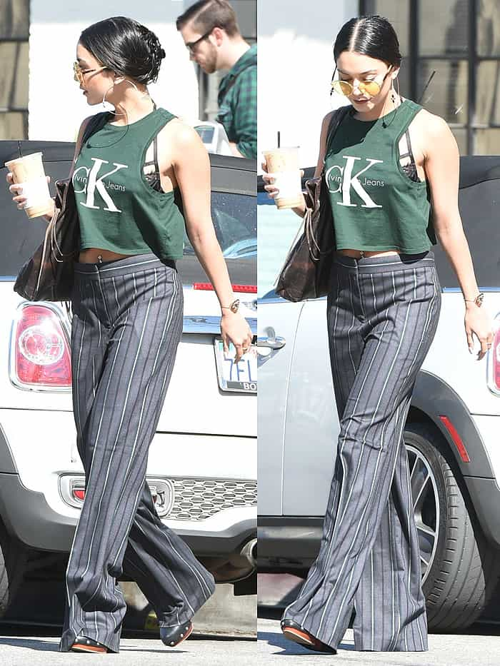 Vanessa Hudgens wearing a CK Jeans crop tank, striped pants, and Vince Camuto 'Elric' sandals while sipping an iced coffee in Los Angeles, California, on March 14, 2017.
