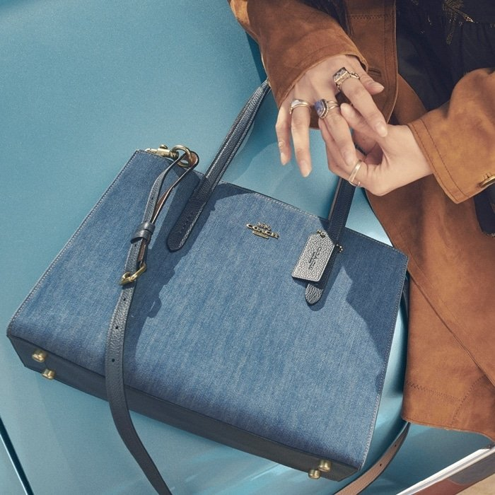The denim Charlie Carryall from COACH is a versatile bag that combines uptown style with downtown cool