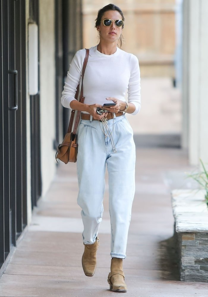 Alessandra Ambrosio wears One Teaspoon mom jeans with a Cotton Citizen ribbed shirt and Re/Done ankle boots